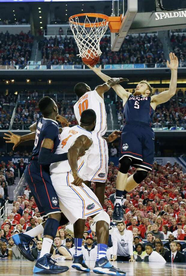 Connecticut guard/forward Niels Giffey (5) shoots as Florida forward Dorian Finney-Smith (10) defends during the second half of the NCAA Final Four tournament college basketball semifinal game Saturday, April 5, 2014, in Arlington, Texas. Photo: Eric Gay, AP / Associated Press