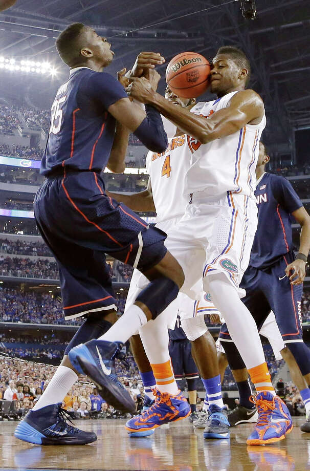 Connecticut center Amida Brimah (35) and Florida forward Will Yeguete (15) go after a loose ball during the second half of the NCAA Final Four tournament college basketball semifinal game Saturday, April 5, 2014, in Arlington, Texas. (AP Photo/Eric Gay) Photo: Eric Gay, ASSOCIATED PRESS / Associated Press