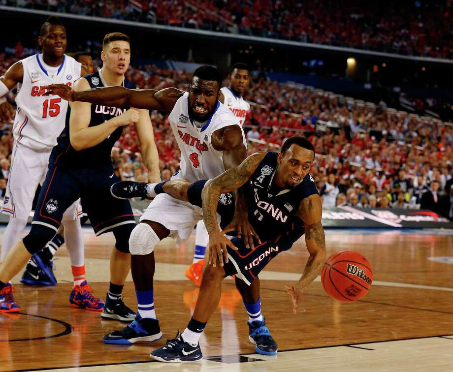 ARLINGTON, TX - APRIL 05:  Ryan Boatright #11 of the Connecticut Huskies and Patric Young #4 of the Florida Gators battle for a loose ball during the NCAA Men's Final Four Semifinal at AT&T Stadium on April 5, 2014 in Arlington, Texas. Photo: Tom Pennington, Getty Images / Getty Images