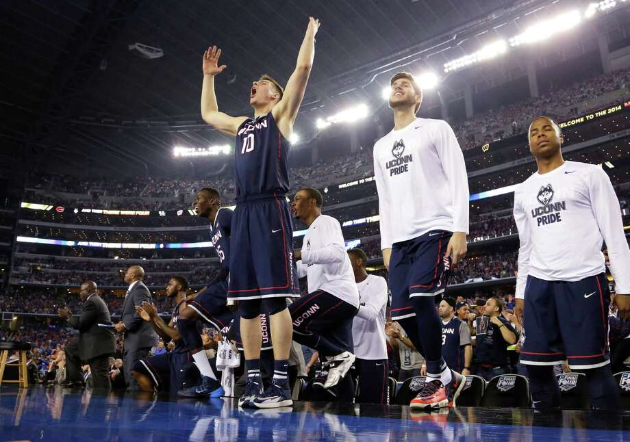 Connecticut forward Tyler Olander (10) celebrates with teammates at the end of an NCAA Final Four tournament college basketball semifinal game against Florida Saturday, April 5, 2014, in Arlington, Texas. Connecticut won 63-53. Photo: Eric Gay, AP / Associated Press