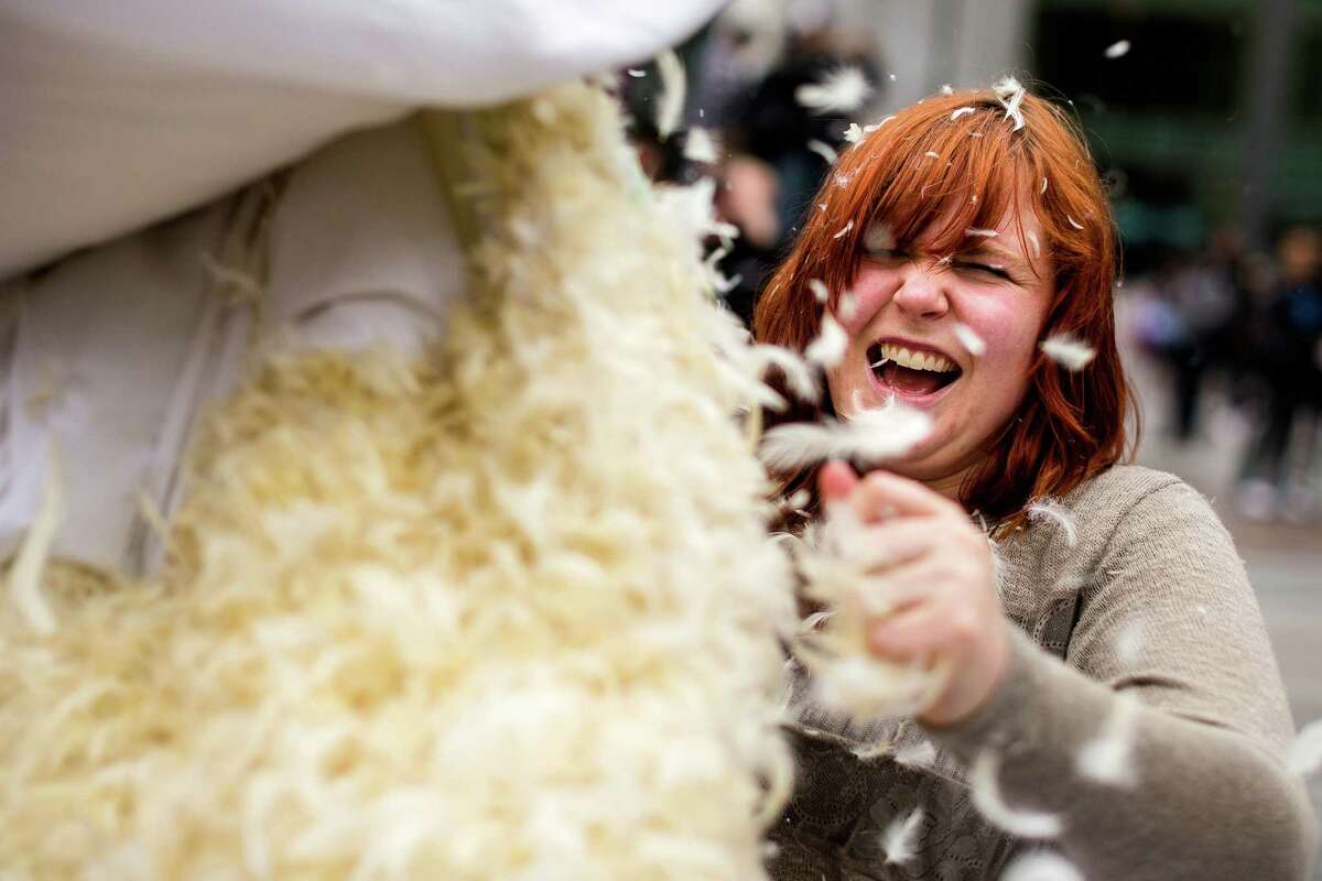 Feathers explode out of a split pillow, mid-swing at the annual International Pillow Fight Day event Saturday, April 5, 2014, at Westlake Park in Seattle. This year's fight was themed superheroes versus villains.
