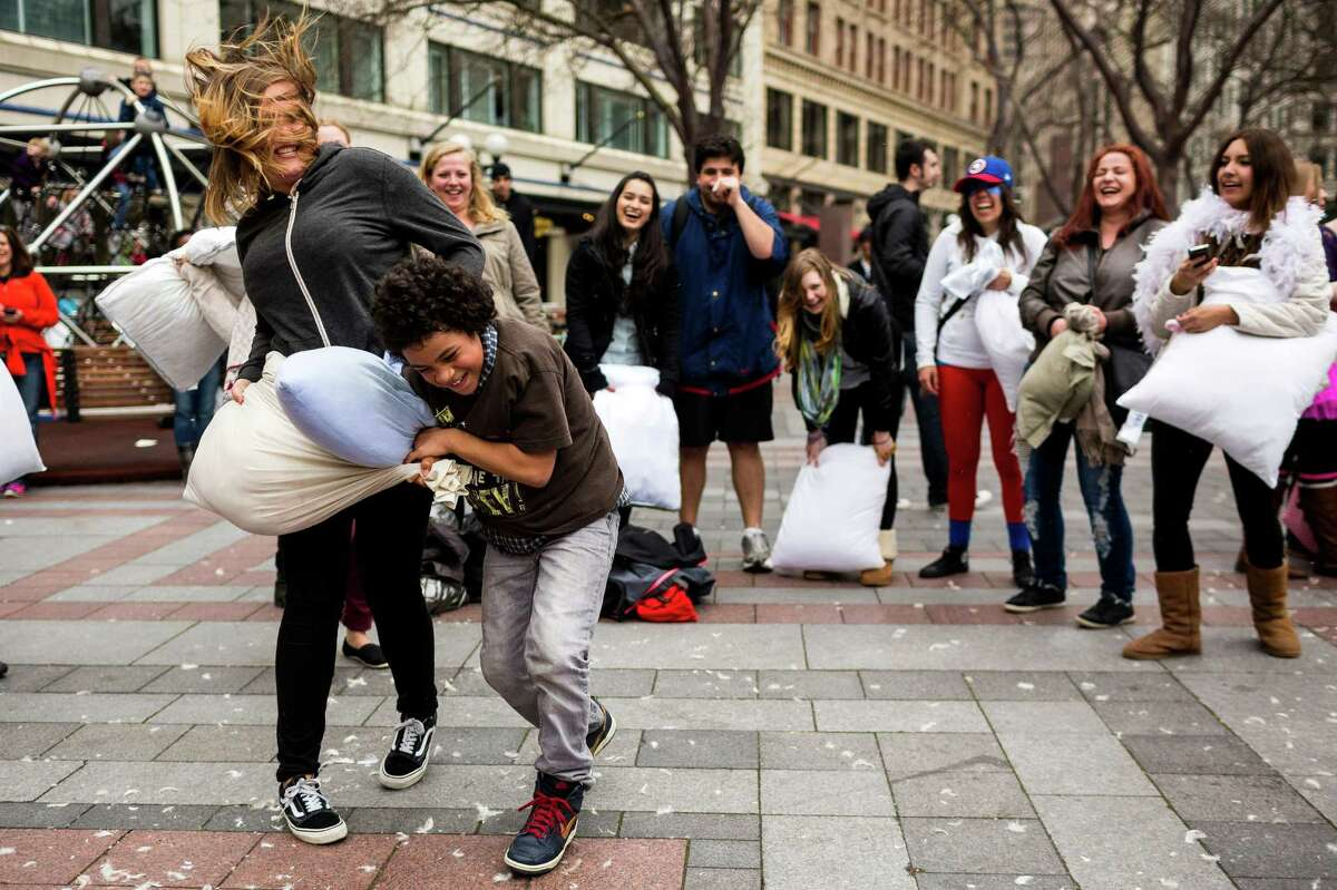 People of all bed sizes took to friendly, feather-soft warfare at the annual International Pillow Fight Day event Saturday, April 5, 2014, at Westlake Park in Seattle. This year's fight was themed superheroes versus villains.