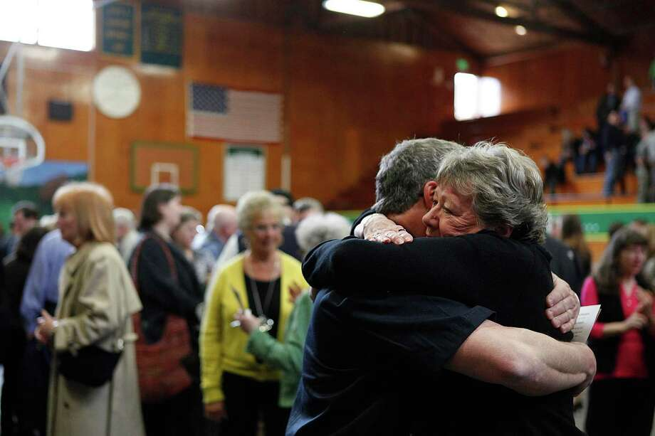 Mourners embrace after Linda McPherson's memorial service at the Darrington Community Center in Darrington, Wash. on Saturday, April 5, 2014. On March 22, she was home reading the newspaper with her husband, Gary McPherson, when a wall of mud buried their home. He was injured but survived. Photo: Sofia Jaramillo, AP / The Herald