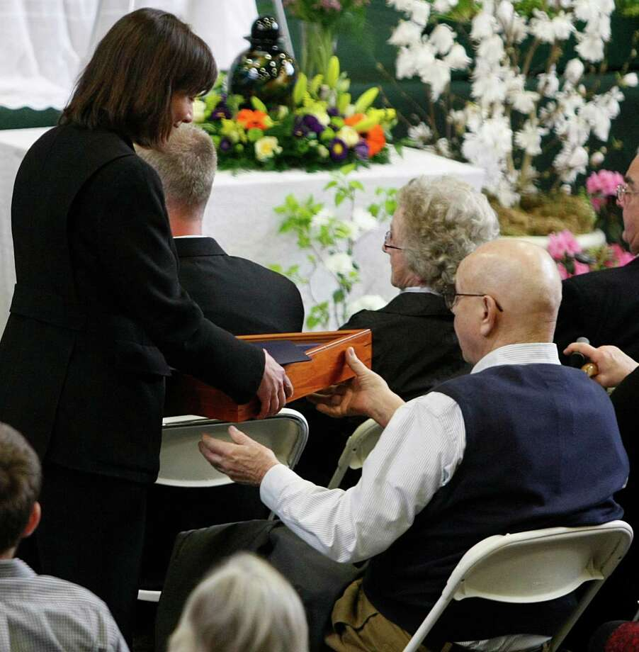 Congresswoman Suzan DelBene, representative of Washington's 1st Congressional District, gives a flag sent from the White House to Gary McPherson during the memorial service for his wife, Linda, at the Darrington Community Center in Darrington, Wash. on Saturday, April 5, 2014. On March 22, she was home reading the newspaper with her husband when a wall of mud buried their home. Photo: Sofia Jaramillo, AP / The Herald