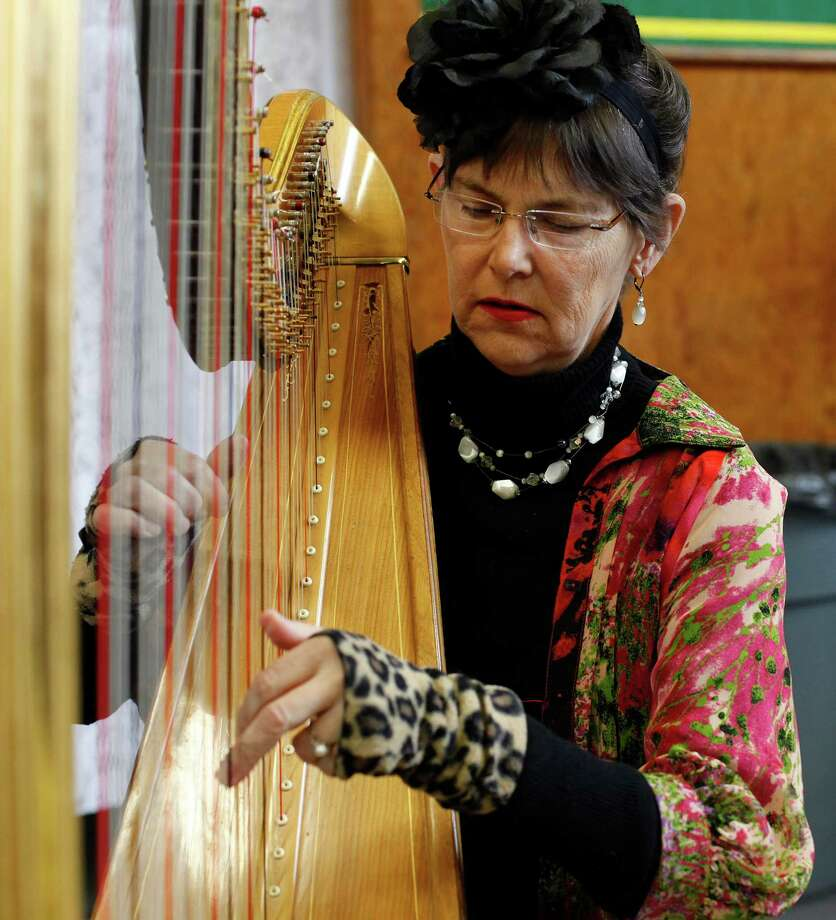 Volunteer harpist Susan McLain plays during Linda McPherson's memorial service at the Darrington Community Center in Darrington, Wash. on Saturday, April 5, 2014. On March 22, she was home reading the newspaper with her husband, Gary McPherson, when a wall of mud buried their home. He was injured but survived. Photo: Sofia Jaramillo, AP / The Herald