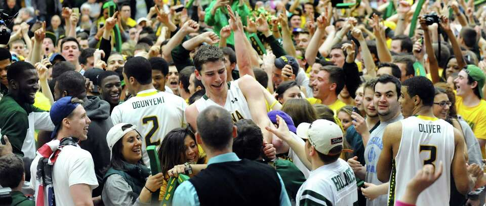 Siena's Rob Poole, center, celebrates their 81-68 win with teammates and fans in the CBI final game