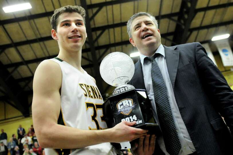 Siena's Rob Poole, left, and coach Jimmy Patsos hold the winner's trophy as the team celebrates thei