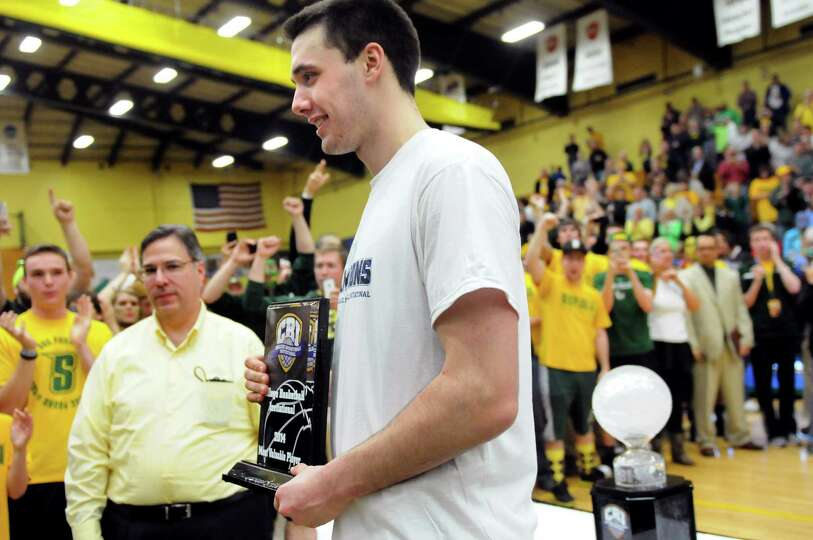 Siena's Brett Bisping, center, holds the MVP award as the team celebrates their 81-68 win over Fresn