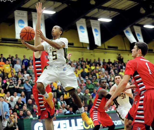 Siena's Evan Hymes, left, goes to the hoop in the CBI final basketball game against Fresno State on
