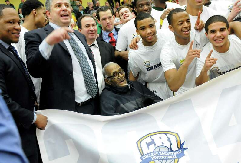 Siena's team poses with Siena Hall of Famer Billy Harrell, center, after they win the CBI final bask