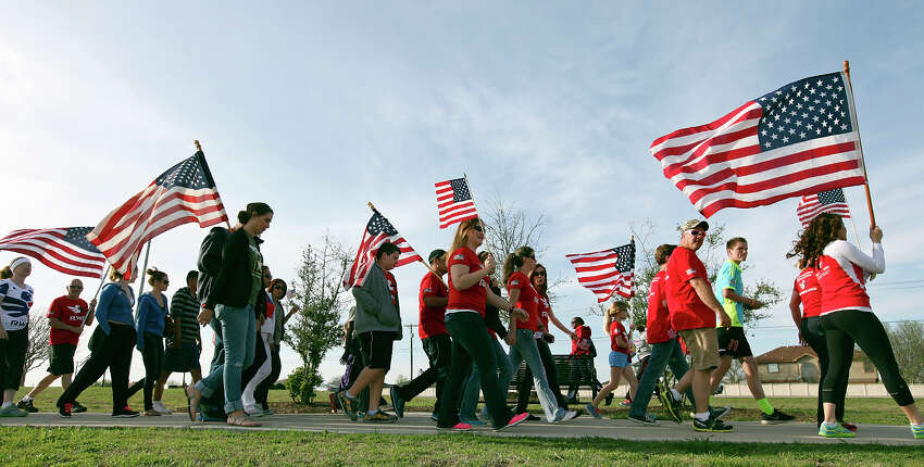 People take part in a flag walk around Lions Club Park in tribute to the Fort Hood shooting victims Friday April 4, 2014 in Killeen, Texas.