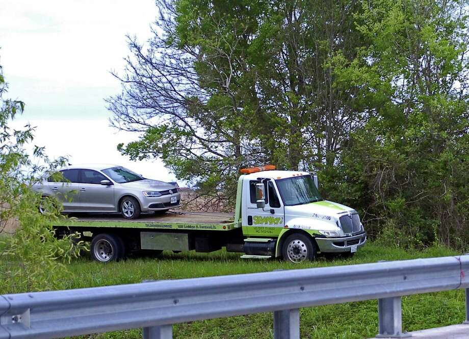 "A wrecker hauls off a Volkswagen Jetta from the scene of a ""suspicious death"" under investigation by Jefferson County Sheriff's Office detectives. The body of an unidentified naked man wrapped in a sheet was found in the car Saturday morning. Photo: Sarah Moore"