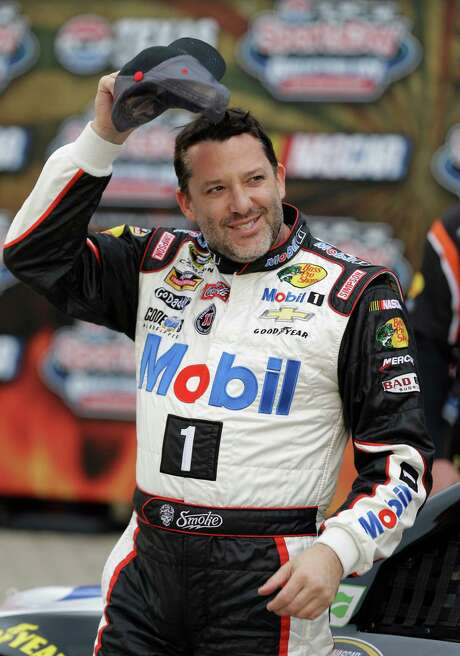 Tony Stewart is in a playful mood after winning the pole for Sunday's Sprint Cup race at Fort Worth. Photo: LM Otero, STF / AP