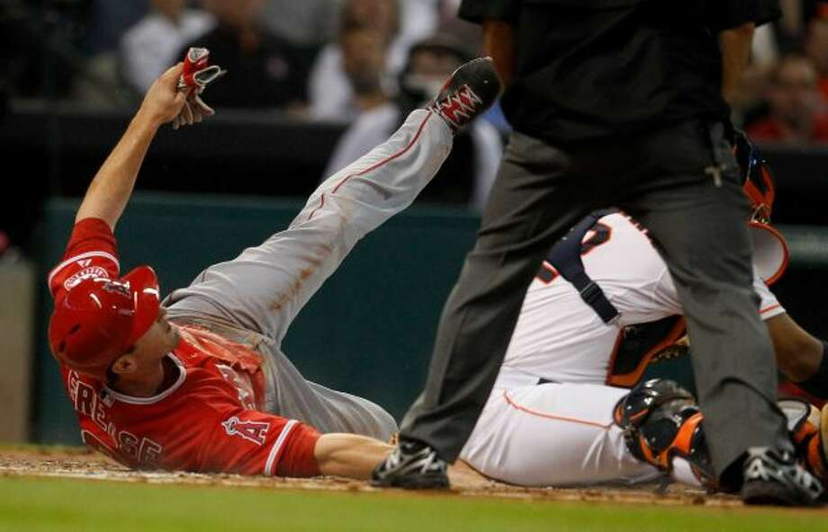 David Freese slides into home, scoring a run.