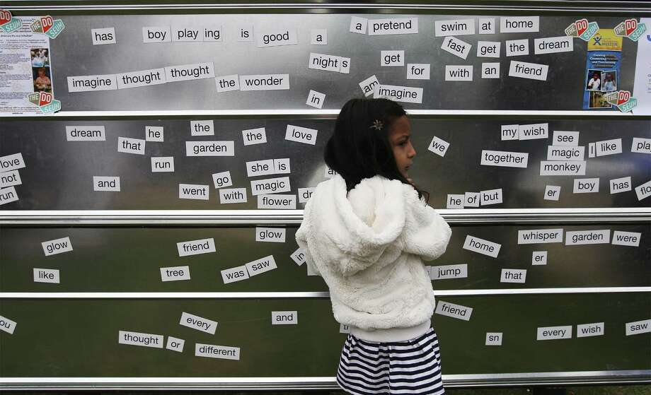 Isabella Cantu, 4, plays on a word wall at the second annual San Antonio Book Festival at Central Library. Photo: Photos By Kin Man Hui / San Antonio Express-News / ©2014 San Antonio Express-News