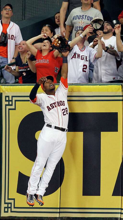 L.J. Hoes of the Astros leaps but cannot make a play on a homer by the Angels' Josh Hamilton. Photo: Bob Levey / Getty Images / 2014 Getty Images