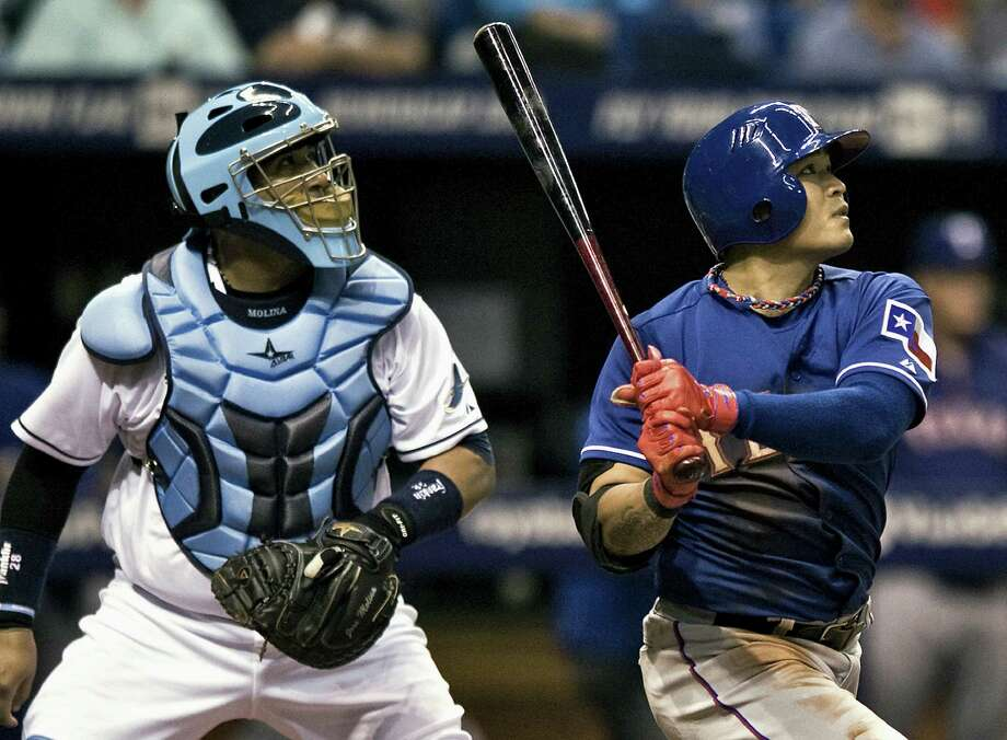 Tampa Bay Rays catcher Jose Molina (left) watches as the Rangers' Shin-Soo Choo hits a run-scoring sacrifice fly to center in the fourth inning. Photo: Steve Nesius / Associated Press / FR69810 AP