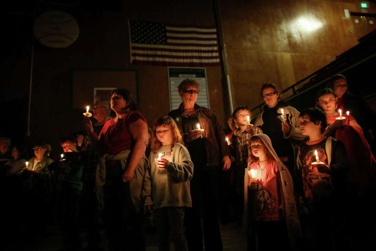 People hold candles during a vigil at the Darrington Community Center on Saturday, April 5, 2014. The vigil was held on the two week anniversary of the Oso mudslide and brought together hundreds of local residents affected by the disaster.