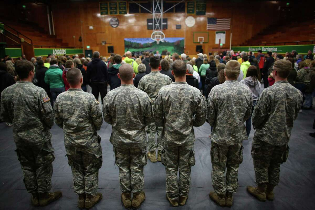 Members of the Washington Army National Guard stand in the back of the room during a vigil at the Darrington Community Center on Saturday, April 5, 2014. The vigil was held on the two week anniversary of the Oso mudslide and brought together hundreds of local residents affected by the disaster.