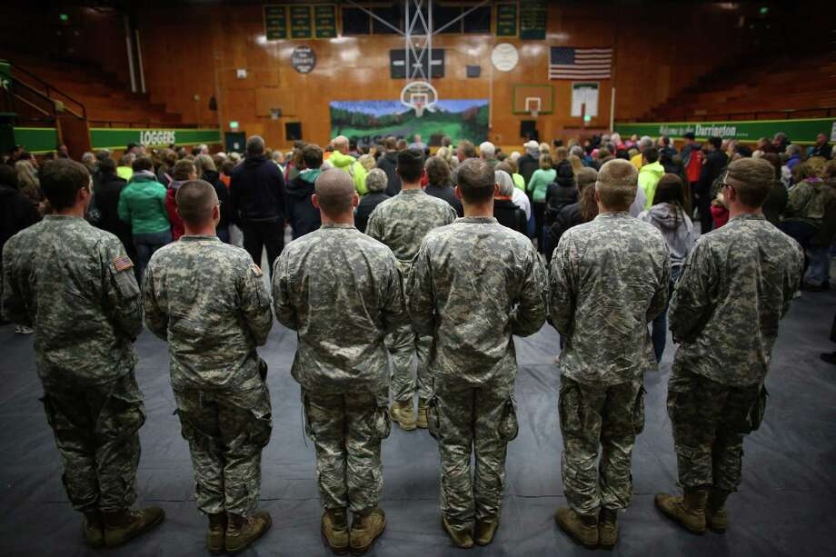Members of the Washington Army National Guard stand in the back of the room during a vigil at the Darrington Community Center on Saturday, April 5, 2014. The vigil was held on the two week anniversary of the Oso mudslide and brought together hundreds of local residents affected by the disaster. Photo: JOSHUA TRUJILLO, SEATTLEPI.COM / SEATTLEPI.COM