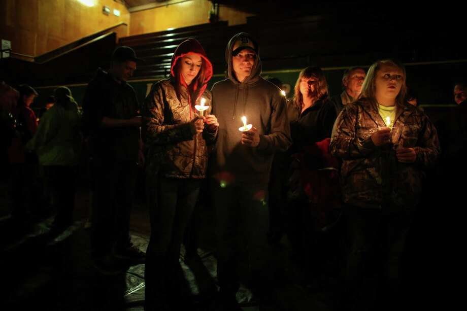People light candles during a vigil at the Darrington Community Center on Saturday, April 5, 2014. The vigil was held on the two week anniversary of the Oso mudslide and brought together hundreds of local residents affected by the disaster. Photo: JOSHUA TRUJILLO, SEATTLEPI.COM / SEATTLEPI.COM