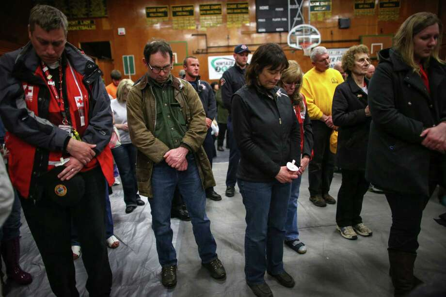 Darrington Mayor Dan Rankin, second from left, and U.S. Representative Suzan DelBene bow their heads during a vigil at the Darrington Community Center on Saturday, April 5, 2014. The vigil was held on the two week anniversary of the Oso mudslide and brought together hundreds of local residents affected by the disaster. Photo: JOSHUA TRUJILLO, SEATTLEPI.COM / SEATTLEPI.COM