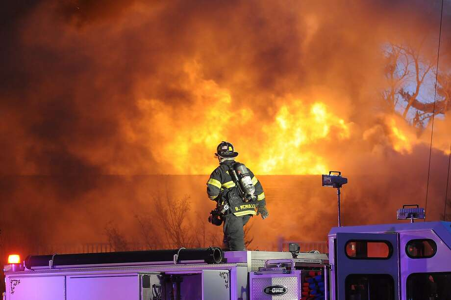A firefighter works on the scene of a multiple alarm fire at the popular Lakeview Pavilion in Foxboro, Mass., Saturday, April 5, 2014. A wedding was taking place at the time of the fire. (AP Photo/The Sun Chronicle, Mark Stockwell) Photo: Mark Stockwell, Associated Press