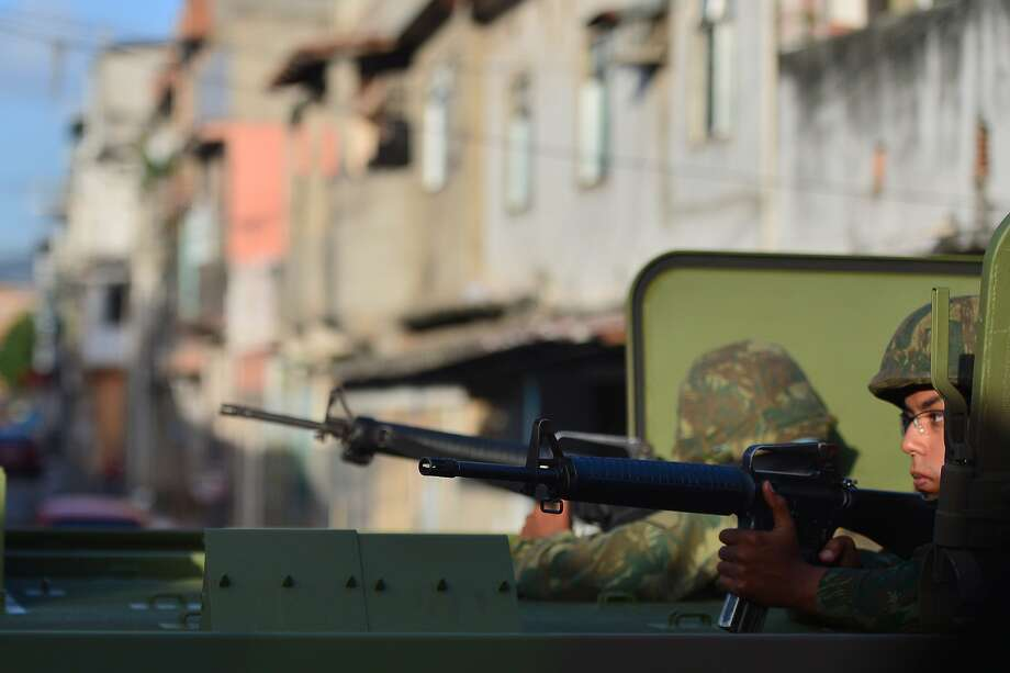 Brazilian soldiers patrol the street during security operations in Vila Pinheiro --part of the Mare shantytown complex near the Galeao (Antonio Carlos Jobim) international airport-- in the north suburb of Rio de Janeiro on April 5, 2014. Thousands of soldiers --including some 2,000 paratroopers, 450 sailors and 200 military police-- in armored vehicles, trucks and on foot entered one of Rio de Janeiro's most notorious slums to provide security less than three months before the World Cup and until July 30.    TOPSHOTS/AFP PHOTO/CHRISTOPHE SIMONCHRISTOPHE SIMON/AFP/Getty Images Photo: Christophe Simon, AFP/Getty Images