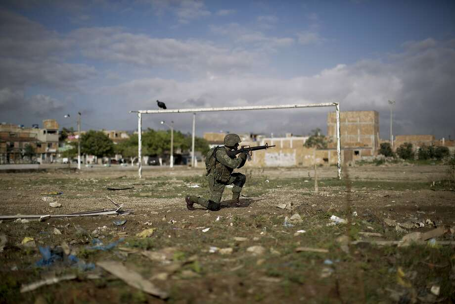 A navy soldier patrols on a soccer field during an operation to occupy the Mare slum complex in Rio de Janeiro, Brazil, Saturday, April 5, 2014. More than 2,000 Brazilian Army soldiers moved into the Mare slum complex early Saturday in a bid to improve security and drive out the heavily armed drug gangs that have ruled the sprawling slum for decades.(AP Photo/Felipe Dana) Photo: Felipe Dana, Associated Press