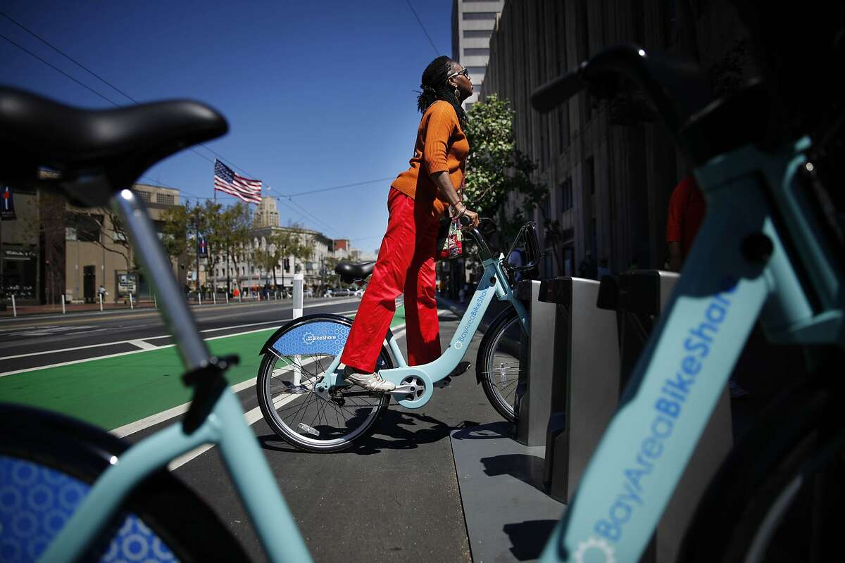 Shela Rowland of San Francisco tries out a Bay Area Bike Share bicycle sitting in a dock at a Bay Area Bike Share station on Market at 10th Street on Thursday, August 29, 2013 in San Francisco, Calif.