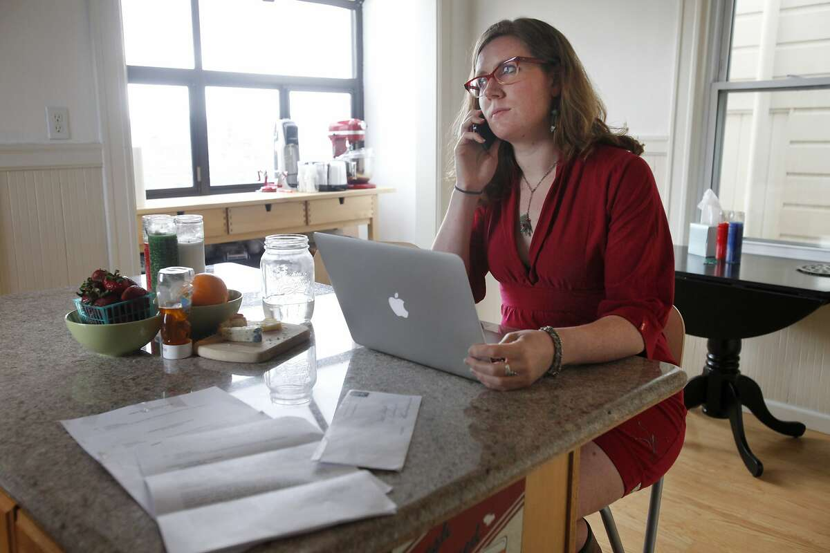 Lisa Weitekamp, 27, listens to a phone message she was hoping may be from a lawyer related to her eviction (didn't end up so) in her kitchen as the eviction notice she and her roommate received days earlier shares counter space with her April 1, 2014 in their apartment in San Francisco, Calif. The two, who have been roommates in the apartment since July, hosted two AirBnB clients for a total of three nights in October 2013. On Thursday, March 27, 2014, they received a 72-hour eviction notice out of the blue.