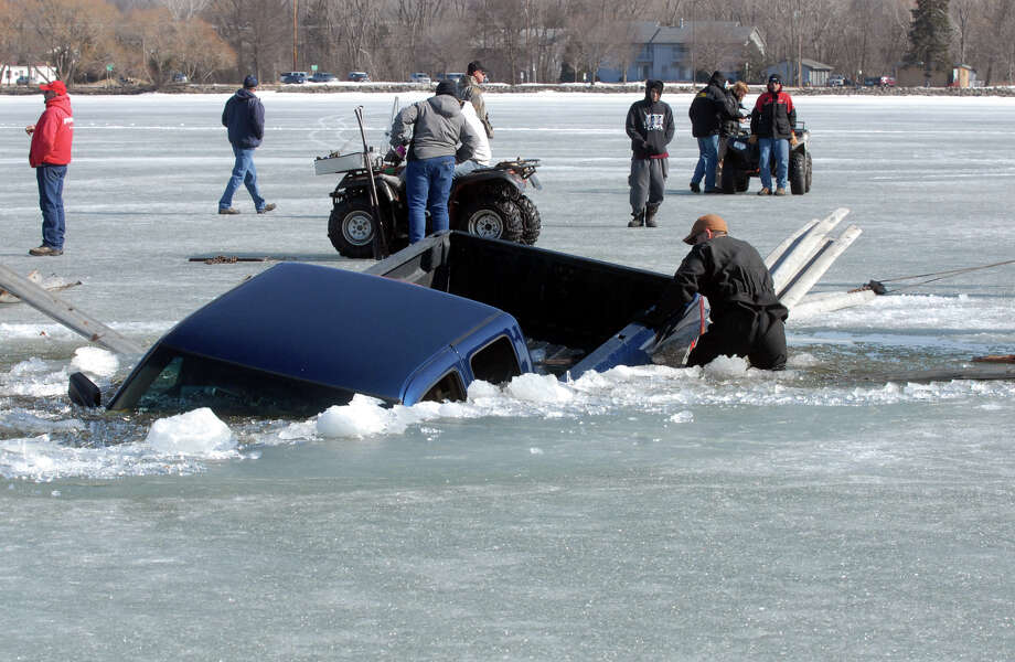 A salvage crew attempts to free a truck from the ice Sunday, March 30, 2014, near Clarence's Harbor at the south end of Lake Winnebago in Fond du Lac, Wis.  Brett Lobajeski said he saw his brother, Robert, break through the ice  and returned to try to help him. But his front tires also broke through the ice about 100 feet from his brother's vehicle.   The two brothers were assisted by snowmobilers on the ice and rescue personnel included members of the Otter Street fishing club who were on the lake removing ramps Sunday. The trucks weren't far from recommended driving paths, but weather that was in the 50s appeared to have caused ice in the area to soften and become fragile. (AP Photo/The Reporter, Carlos Munoz)  Photo: Carlos Munoz, AP  / The Reporter