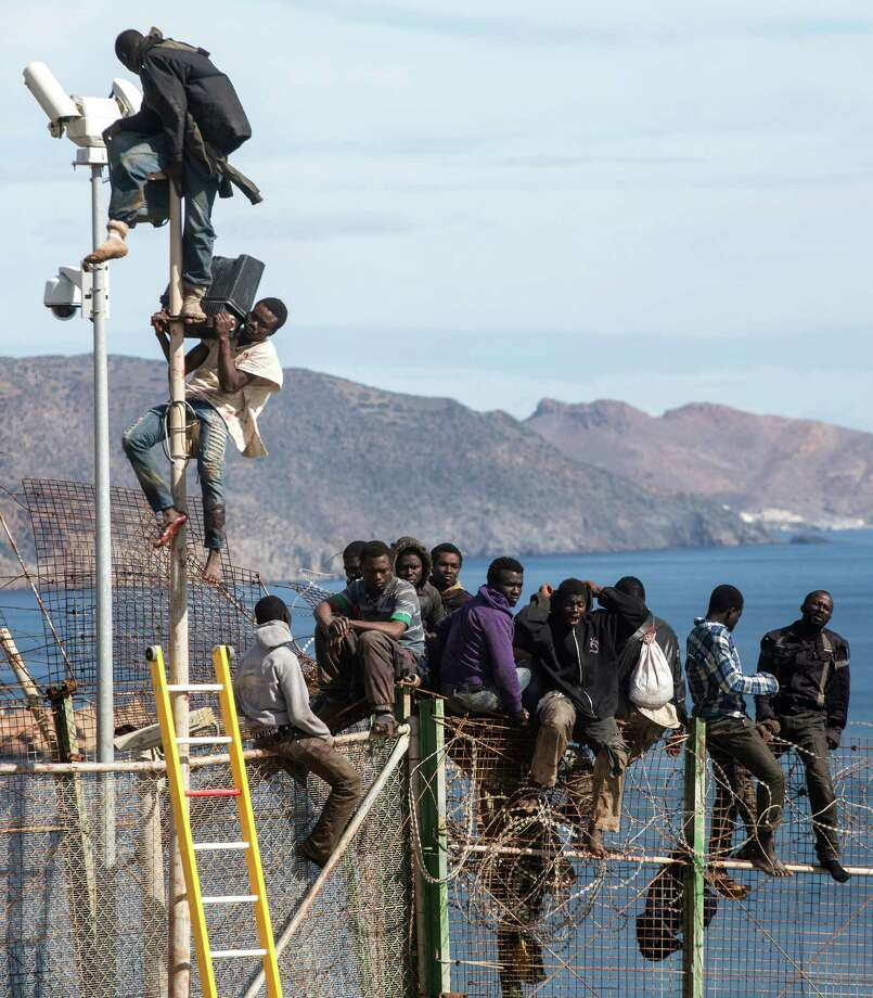 Sub-Saharan migrants sit on top of a metallic fence that divides Morocco and the Spanish enclave of Melilla on Thursday April 3, 2014. Spanish and Moroccan police have thwarted a fresh attempt by dozens of African migrants to try to scale border fences to enter the Spanish enclave of Melilla. Thousands of sub-Saharan migrants seeking a better life in Europe are living illegally in Morocco and regularly try to enter Melilla in the hope of later making it to mainland Spain. Photo: Santi Palacios, AP  / AP