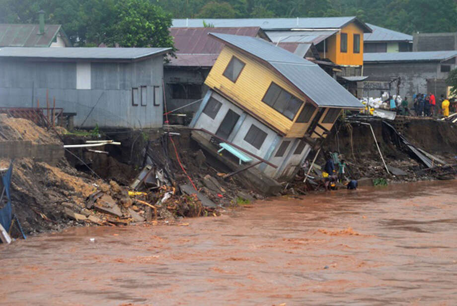 In this Friday, April 4, 2014 photo, a building teeters on the edge of a river in Honiara, Solomon Islands. Flash floods in the Solomon Islands have killed 14 people and left thousands more homeless, authorities said Saturday. (AP Photo/Solomon Star) Photo: AP  / Solomon Star