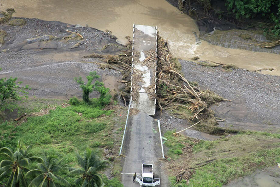 In this Saturday, April 5, 2014 photo, a bridge is seen collapsed after flooding in west Guadalcanal Solomon Islands. Flash floods in the Solomon Islands have killed 14 people and left thousands more homeless, authorities said Saturday. (AP Photo/Solomon Star)  Photo: AP  / Solomon Star