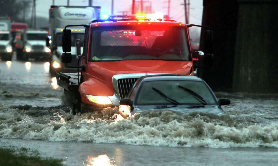 A wrecker pushes a driver to safety as she steers her way out from a flooded patch of road, Wednesday, April 2, 2014, in St. Louis. High waters stranded three vehicles. No one was injured. (AP Photo/St. Louis Post-Dispatch, Laurie Skrivan)  Photo: Laurie Skrivan, AP  / St. Louis Post-Dispatch