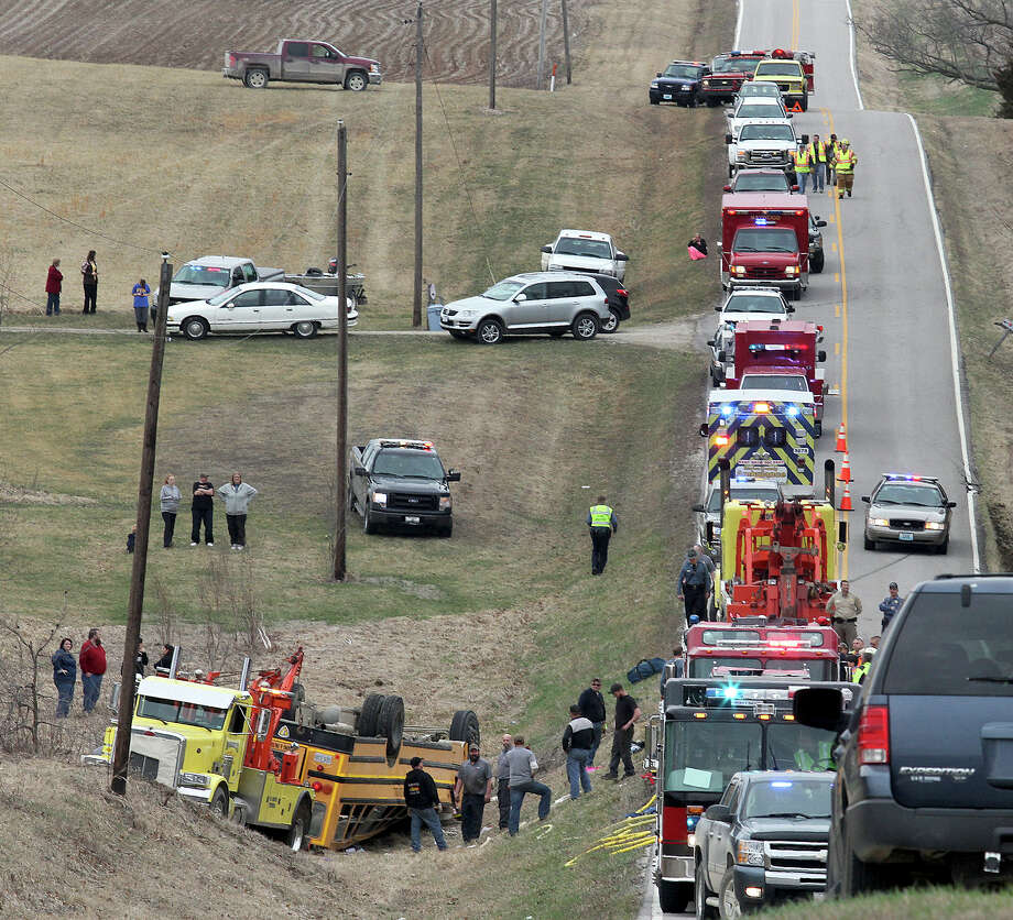 Emergency response personnel work at the scene of an overturned school bus near the rural northeast Missouri town of Ewing near the Illinois border Tuesday, April 1, 2014. Nearly two dozen students were injured who attended Highland Elementary and Highland High schools in the Lewis County C-1 District. Ewing is located about 125 miles northwest of St. Louis. Photo: Steve Bohnstedt, AP  / Quincy Herald Whig