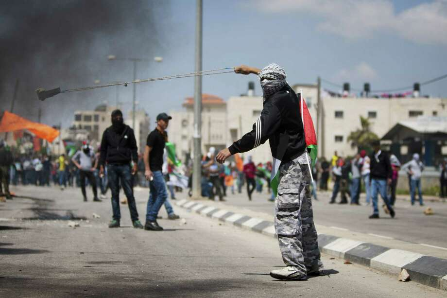 A masked Palestinian uses a slingshot to hurl stones toward Israeli soldiers during a protest calling for the release of Palestinian prisoners held in Israeli jails, outside Ofer, an Israeli military prison near the West Bank city of Ramallah, Friday, April 4, 2014. Photo: Majdi Mohammed, AP  / AP