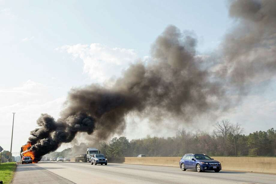 Traffic passes a burning tractor-trailer on Interstate 75 southbound near Exit No. 228, in Stockbridge, Ga., on Tuesday, April 1, 2014. The blaze later shut down all southbound lanes. The trailer was owned by Ira Higdon grocery stores, based in Cairo, Ga. No injuries were reported. Photo: Kevin Liles, AP  / FR170929 AP