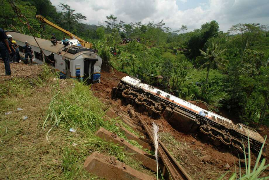 Worker remove derailed trains in Tasikmalaya, West Java, Indonesia, Saturday, April 5, 2014. A passenger train hit mounds of mud triggered by a landslide and derailed in central Indonesia, killing at least three people and injuring seven, a railway official said Saturday. Photo: Erwin Gobel, AP  / AP2014