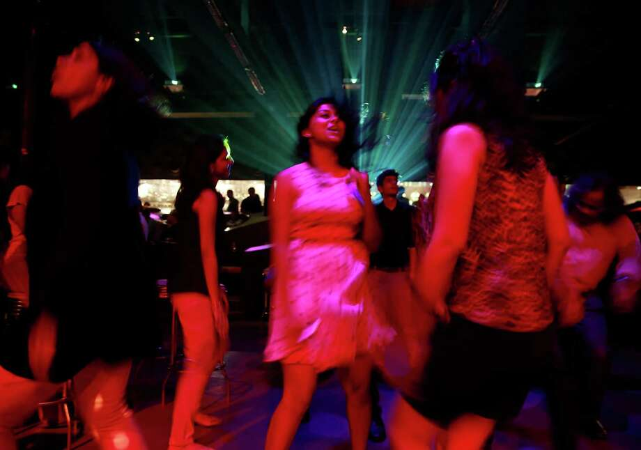"In this Wednesday, April 2, 2014 photo, young Indian women dance at a night club ""blueFROG"" in Mumbai, India. As India begins its weekslong election process Monday, April 7, the enormous population of ambitious, tech-savvy and politically engaged youths has more potential than ever to sway the outcome. More than 378 million of India's 814 million eligible voters between 18 and 35, according to census records. Photo: Rafiq Maqbool, AP  / AP2014"