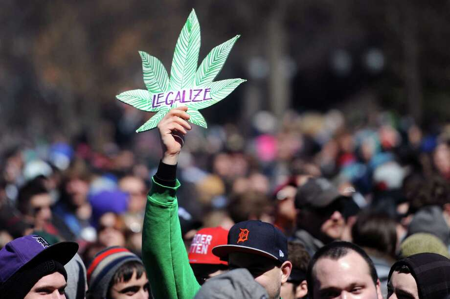 A man holds up a sign advocating the legalization of marijuana at the 43rd annual Hash Bash on the University of Michigan Diag in Ann Arbor, Mich. Saturday, April 5, 2014. Photo: Brianne Bowen, AP  / The Ann Arbor News
