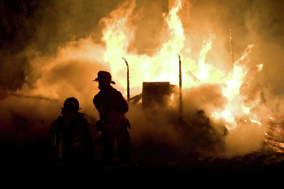 Firefighters try to put out a early morning fire on Friday, April 4, 2014 outside Danville, Pa.  The early morning farmhouse fire in north-central Pennsylvania killed three children, ages 2 to 13, authorities said.  The Northumberland County coroner identified the victims as 13-year old Daniel Dissinger, 7-year old Gavin Dissinger and 2-year old Arthur Dissinger. The deaths were ruled accidental. The children's mother was at work at the time of the fire, Kriner said. He said a 13-year-old boy and 14-year-old girl managed to escape from the home and were treated for injuries that weren't life-threatening. Another child was staying at a friend's house overnight, he said. The home had almost completely collapsed by the time the first crews arrived, officials said. Photo: Larry Deklinski, AP  / The News-Item