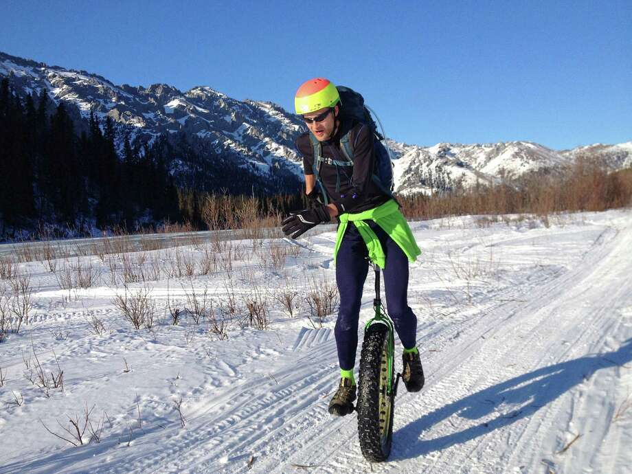 In this photo taken Sunday, March 30, 2014 and provided by Ed Plumb, unicyclist Elliott Wilson leaves a checkpoint during the White Mountains 100-mile ultra-marathon, north of Fairbanks, Alaska. When Wilson decided to ride a unicycle in the White Mountains 100 endurance race, he knew it was an off-the-wall idea. After all, most people wouldn't think about riding 100 miles on snowmachine and dog mushing trails in late March in Fairbanks on two wheels, much less one. Wilson succeeded, much to the surprise of himself, as well as some of Fairbanks' foremost two wheelers. Photo: Ed Plumb, AP  / Ed Plumb