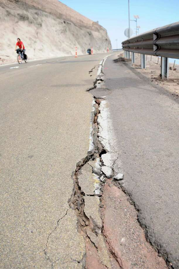 Cracks line a road after an earthquake near Alto Hospicio, Chile, Thursday, April 3, 2014. A magnitude-8.2 earthquake hit Chile's Pacific coast late Tuesday, followed by daily aftershocks. (AP Photo/Cristian Vivero)  Photo: Cristian Vivero, AP  / AP2014