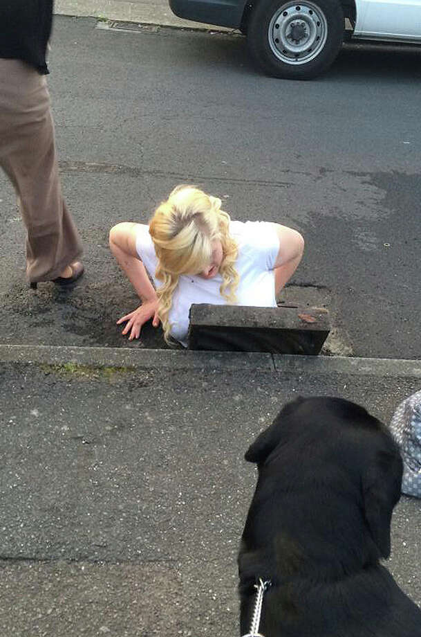 In this image taken by witness to the occurrence Tim Richards on Wednesday April 2, 2014 shows  Ella Birchenough being rescued by firefighters after getting stuck in a storm drain while trying to retrieve her mobile phone in Dover southeast England .  Sixtenn-year-old Ella Birchenough  squeezed down the hole to try to fetch her phone, but she became stuck fast in front of a group of amused onlookers, including her mother, according to witness Tim Richards. (AP Photo/Tim Richards/PA)  Photo: Tim Richards, AP  / PA
