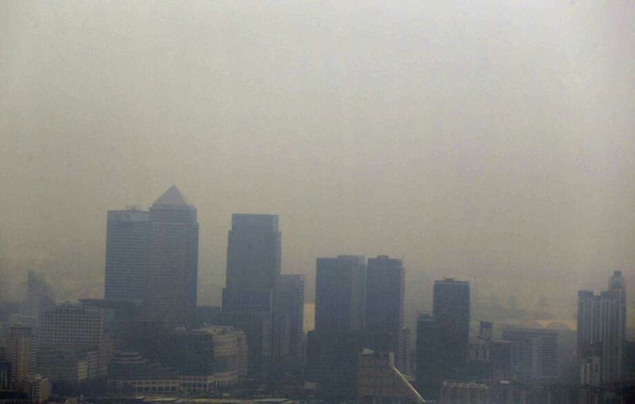The skyscrapers of the Canary Wharf business district in London are shrouded in smog, as seen from a viewing gallery of a skyscraper in central London, Thursday, April 3, 2014. British authorities have warned people with heart or lung conditions to avoid exertion as a combination of industrial pollution and Sahara dust blankets the country in smog. The environment department said air pollution level could reach the top rung on its 10-point scale. The pollution is expected to ease by Friday. Photo: Lefteris Pitarakis, AP  / AP2014
