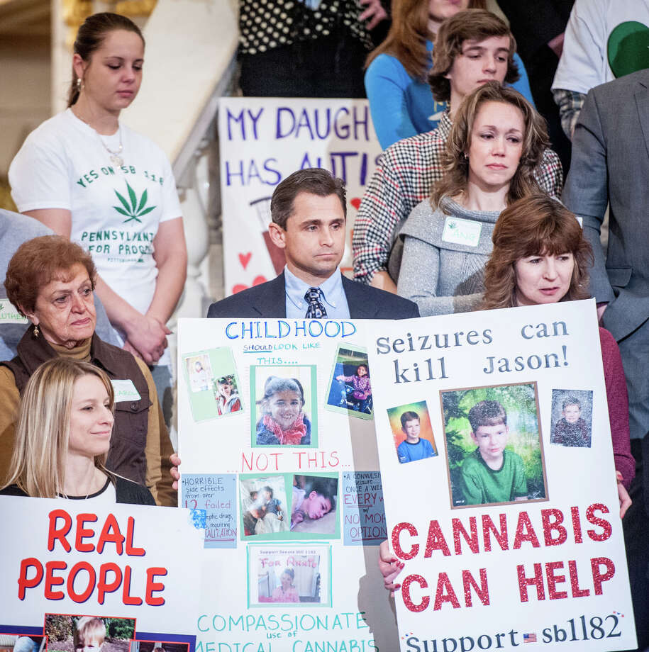In this photo taken on Monday, March 31, 2014, Matt Sharrer, center, and wife Angie, center right, were among the supporters of cannabis reform at rally at the Capitol rotunda in Harrisburg, Pa. The Sharrer's have a 9-year-old daughter, Annie, who suffers from a form of epilepsy, a condition that cannabis oil as he been reported to help ease seizures related to the illness. Photo: Jeff Lautenberger, AP  / Evening Sun
