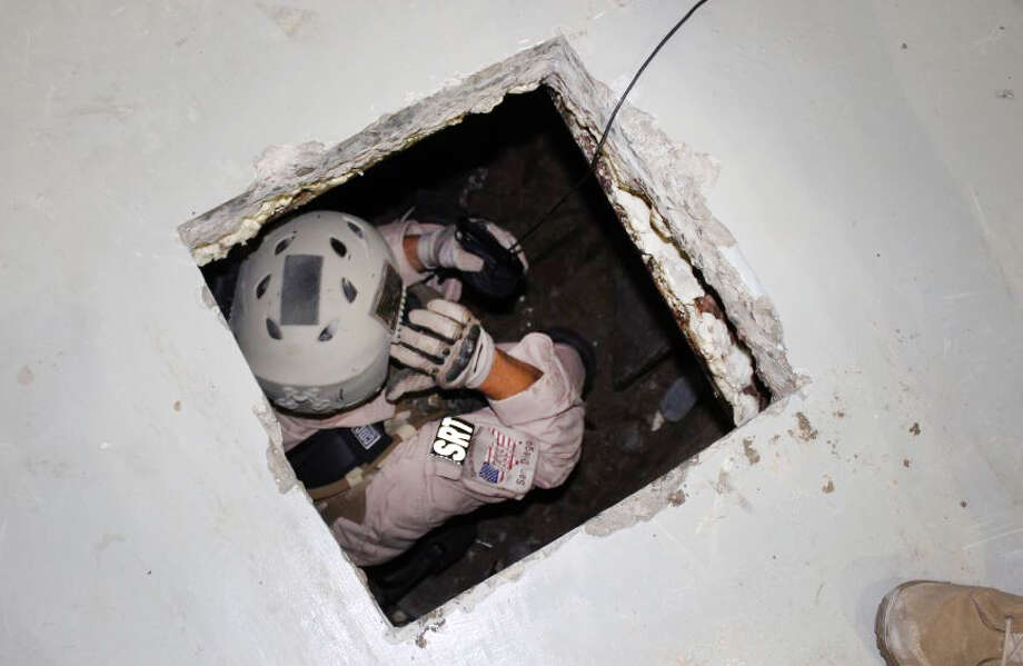 This image provided by the U.S. Immigration and Customs Enforcement (ICE) agency shows an agent examining one of two tunnels discovered April 1, 2014 in San Diego's Otay Mesa industrial park. The first tunnel, stretching about 600 yards, was discovered on Tuesday. Authorities say it was equipped with lighting, a crude rail system and wooden trusses. The other tunnel was discovered Thursday. It's described as stretching more than 700 yards and more sophisticated, with an electric rail system and ventilation equipment. Photo: Uncredited, AP  / AP2014