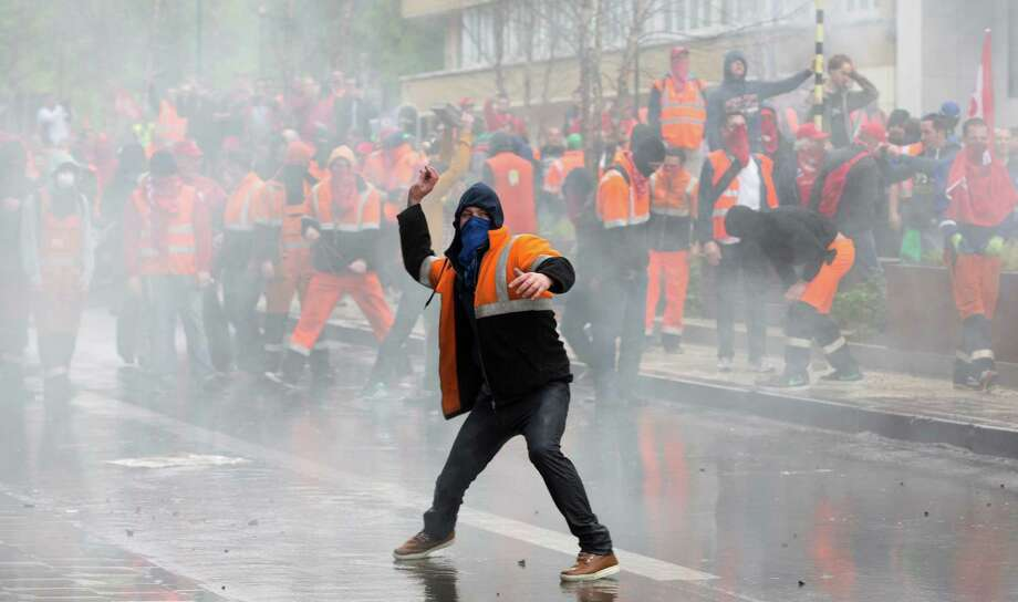 A protestor hurls a rock toward police officers during a trade union demonstration in the European Quarter of Brussels on Friday, April 4, 2014. A demonstration by labor unions demanding a better deal for Europe's working men and women led to street clashes in Brussels Friday, with some protesters showering police with oranges and cobblestones and police responding with water cannon. Photo: Virginia Mayo, AP  / AP
